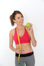 Fitness girl succeeding diet holding green apple, isolated Royalty Free Stock Photo
