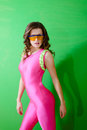 Fitness girl wearing pink lycra jumpsuit and portrait of sexy young lady big safety glasses on green background half length of Royalty Free Stock Photo