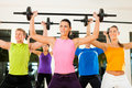 Fitness group with barbell in gym Royalty Free Stock Image
