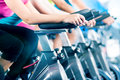 Fitness group indoor bicycle cycling in gym of four people spinning the exercising their legs doing cardio training Royalty Free Stock Photos