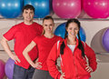Fitness group portrait of three young sport people with ball back Royalty Free Stock Images