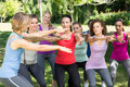 Fitness group squatting in park on a sunny day Stock Images