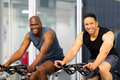 Fitness guys biking in gym Royalty Free Stock Photos