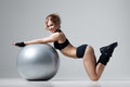 Fitness with gym ball athletic woman lies on a on gray background Royalty Free Stock Image