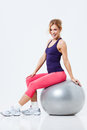 Fitness with gym ball athletic woman sitting on a on gray background Royalty Free Stock Photos