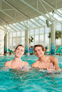 Fitness gymnastics under water in swimming pool a young couple man and woman doing sports and or aerobics or spa with Stock Photos