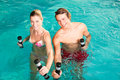 Fitness gymnastics under water in swimming pool a young couple man and woman doing sports and or aerobics or spa with Royalty Free Stock Image