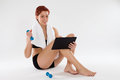 Fitness information from the internet happy woman getting with a tablet computer holding dumbbell Stock Photos
