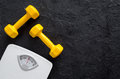 Fitness for losing weight. Bathroom scale and dumbbell on black background top view Royalty Free Stock Photo