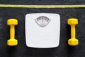 Fitness for losing weight. Bathroom scale, measuring tape and dumbbell on black background top view Royalty Free Stock Photo
