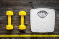 Fitness for losing weight. Bathroom scale, measuring tape and dumbbell on wooden background top view Royalty Free Stock Photo