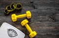 Fitness for losing weight. Bathroom scale, measuring tape and dumbbell on wooden background top view copyspace Royalty Free Stock Photo
