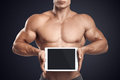 Fitness male holding horizontally digital tablet with blank scre Royalty Free Stock Photo