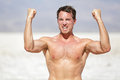 Fitness man showing muscles cheering outside in desert in extreme hot weather muscular masculine male sports model flexing Royalty Free Stock Photo