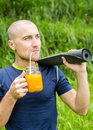 Fitness man with yoga mat holding a glass of orange juice Royalty Free Stock Photo