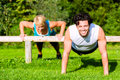 Fitness people doing pushups for sport young men and women or personal trainer exercising in city park Stock Images