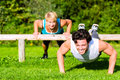 Fitness people doing pushups for sport young men and women or personal trainer exercising in city park Stock Image