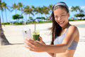 Fitness selfie woman drinking green smoothie vegetable taking self portrait photograph with smart phone after running exercise Royalty Free Stock Images