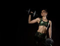 Fitness sexy girl with dumbbells on a dark background. Athlete doing exercises in the gym. Free space for your text Royalty Free Stock Photo
