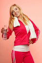 Fitness sport woman white towel on shoulders studio shot portrait smiling happy female sporty girl with and bottle of water pink Royalty Free Stock Photos