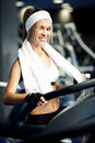 Fitness on a treadmill smiling athletic woman exercising Royalty Free Stock Images