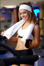 Fitness on a treadmill smiling athletic woman resting Royalty Free Stock Image