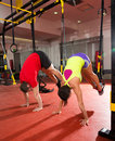 Fitness trx training exercises at gym woman and man crossfit women men push up pushup Stock Photos