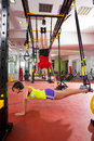 Fitness trx training exercises at gym woman and man crossfit women push up dip rings men workout Royalty Free Stock Images