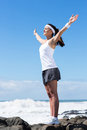 Fitness woman arms up young stretching on beach Stock Images