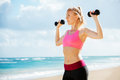 Fitness woman with barbells working out exercising outdoors at the beach Royalty Free Stock Photography