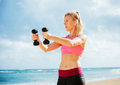 Fitness woman with barbells working out exercising outdoors at the beach Stock Photo