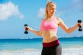 Fitness woman with barbells working out exercising outdoors at the beach Royalty Free Stock Images
