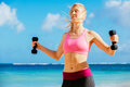 Fitness woman with barbells working out exercising outdoors at the beach Royalty Free Stock Photos