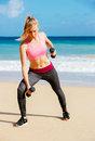 Fitness woman with barbells working out exercising outdoors at the beach Stock Images