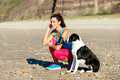 Fitness woman and dog on beach relaxed with listening music with sport arm band earphones at the sporty girl taking a breath Stock Photography