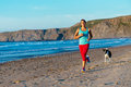 Fitness woman and dog running on beach workout at the sporty female runner training summer sunset Royalty Free Stock Images