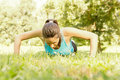 Fitness woman doing push ups in the park Royalty Free Stock Photos