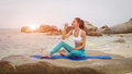 Fitness woman drink water after doing sport exercises on beach at sunset. Royalty Free Stock Photo