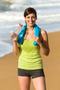 Fitness woman drinking happy beautiful water and sweating after exercising on summer hot day in beach female athlete smiling after Royalty Free Stock Photos