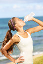 Fitness woman drinking water after beach running at thirsty sport runner resting taking a break with bottle drink outside Royalty Free Stock Image