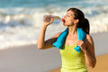 Fitness woman drinking water on summer beautiful and sweating after exercising hot day in beach female athlete after work out Royalty Free Stock Photo