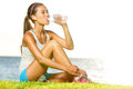 Fitness woman drinking water after workout outside running training by ocean sea beautiful sweaty fit model sitting in Royalty Free Stock Image