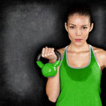 Fitness woman exercising crossfit holding kettlebell strength training biceps beautiful sweaty instructor on blackoard Stock Photo