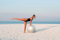 Fitness woman with fit ball on beach outdoors. Royalty Free Stock Photo