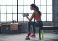 Fitness woman lifting dumbbell in urban loft gym Royalty Free Stock Photo