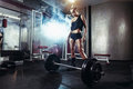 Fitness woman prepares for exercising with barbell in gym Royalty Free Stock Photo