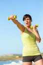 Fitness woman punching and training working out on beach in summer sporty girl boxing with dumbbells hard exercising Royalty Free Stock Image