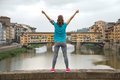 Fitness woman rejoicing in front of ponte vecchio in florence i italy rear view Stock Photos