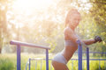 Fitness woman relax after workout exercises on bars outdoor Royalty Free Stock Photo
