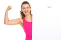 Fitness woman showing biceps and blank billboard happy young Royalty Free Stock Photo